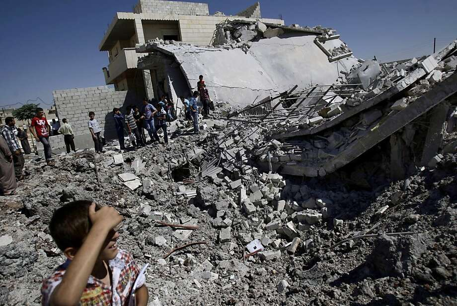 Syrians gather by the rubble of a house, destroyed from Syrian forces shelling early Monday, in the Syrian town of Azaz, on the outskirts of Aleppo, Monday, Sept. 3, 2012. (AP Photo/Muhammed Muheisen) Photo: Muhammed Muheisen, Associated Press