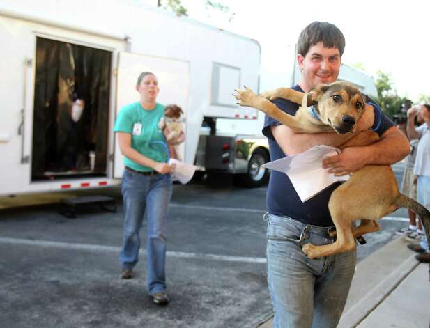 Sonny Cromer,  an employee with the Houston SPCA,  carries a dog from the truck as members of the SPCA unload cats, dogs, puppies, kittens, and bunnies, all evacuees from the effects of Hurricane Issac, at the SPCA, Monday, Sept. 3, 2012, in Houston. Photo: Karen Warren, Houston Chronicle / © 2012  Houston Chronicle