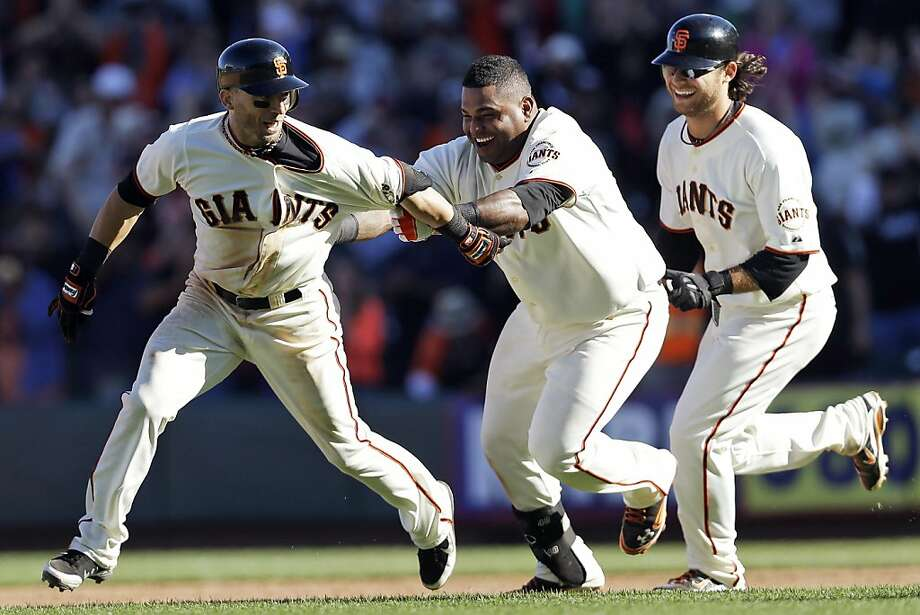 Pablo Sandoval (center) and Brandon Crawford chase Marco Scutaro after Scutaro's base hit brought home Crawford. Photo: Marcio Jose Sanchez, Associated Press