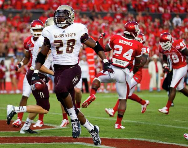 Texas State running back Marcus Curry (28) runs past Houston defensive back Kent Brooks (24) as he crosses the goal line for a two-yard touchdown run during the first quarter of an NCAA college football game at Robertson Stadium, Saturday, Sept. 1, 2012, in Houston. (AP Photo/Houston Chronicle, Brett Coomer) Photo: Brett Coomer, Associated Press / Houston Chronicle