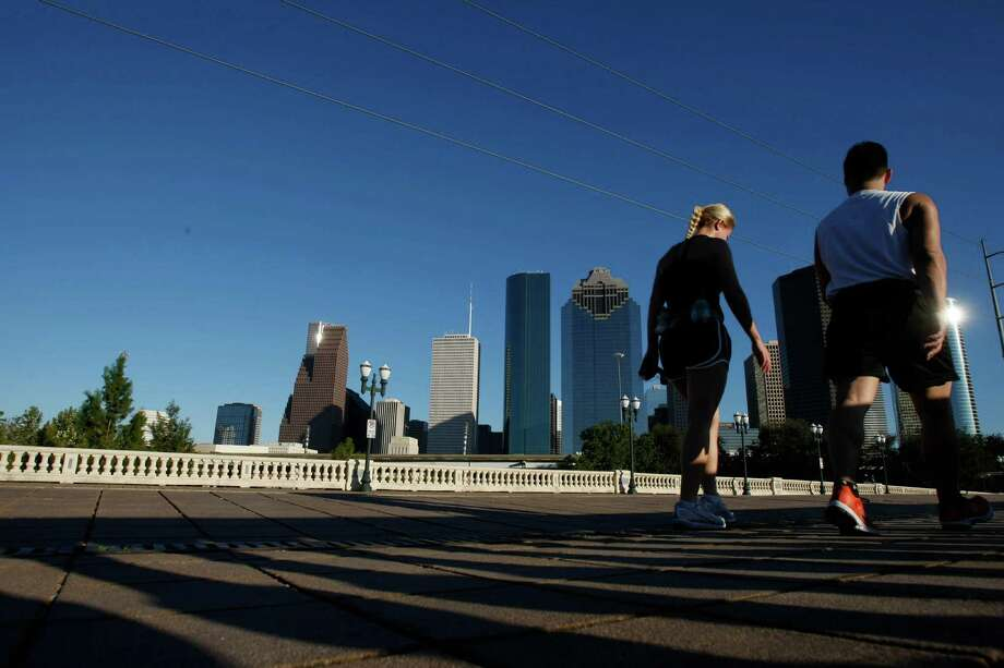 Walkers cross the Sabine Street Bridge on a day of moderate temperatures and no precipitation Monday, Nov. 2, 2009,  in Houston. If current projections hold the eight county region of Greater Houston will meet the Federal limits for SMOG. ( Nick de la Torre / Chronicle ) Photo: Nick De La Torre / Houston Chronicle