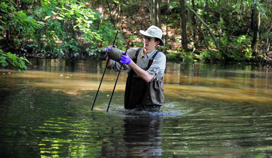 Geoff Giller, a second year master's student at the Yale School of Forestry & Environmental Studies, recovers a sampling device left in a backyard pond on Kazo Drive in Shelton for the past month measuring the water chemistry Tuesday, August 28, 2012.   Giller is looking at pollution in suburban backyard ponds and how it affects frog populations and and deformities in the species. Photo: Autumn Driscoll / Connecticut Post