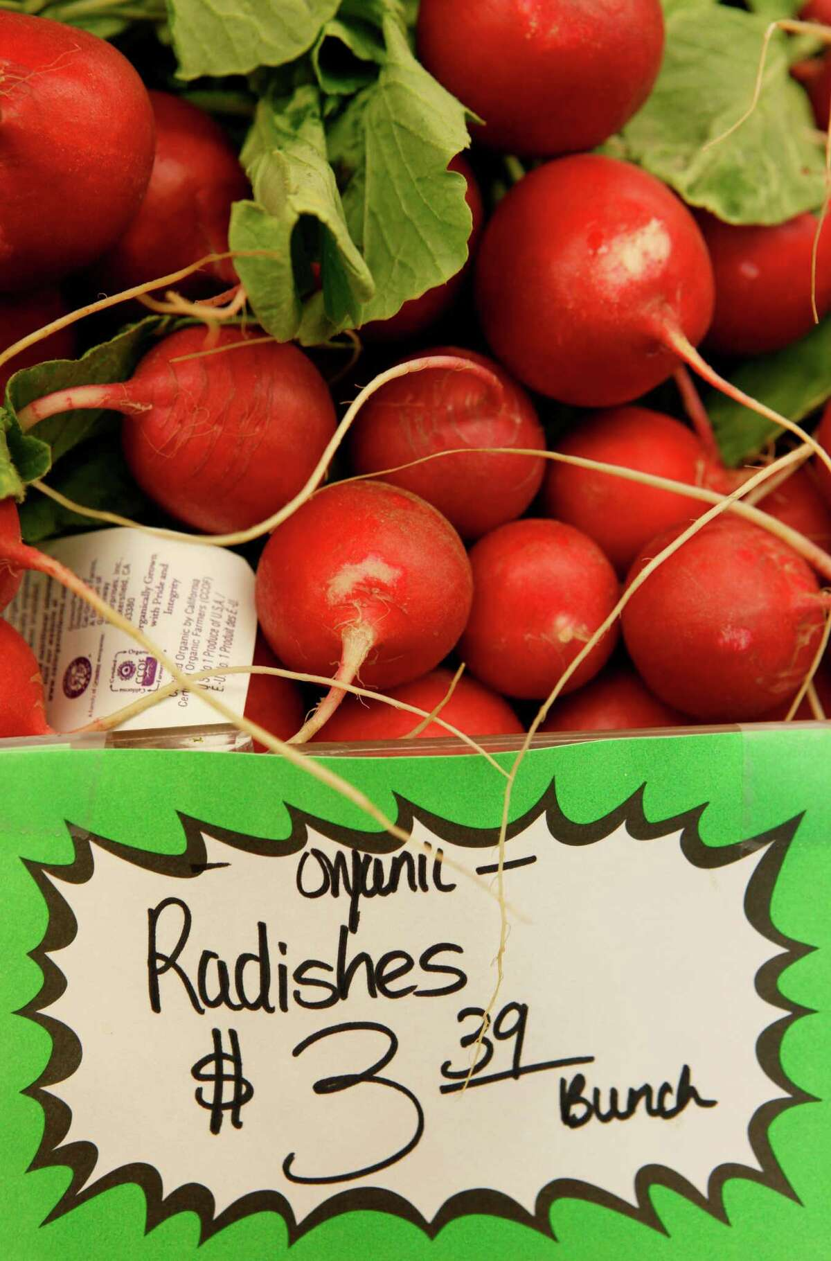 FILE - HOLD FOR RELEASE UNTIL 5:00 P.M. EDT AND THEREAFTER ON SEPT. 3, 2012 - This March 16, 2011, file photo shows organic radishes at the Pacifica Farmers Market in Pacifica, Calif. Patient after patient asked: Is eating organic food, which costs more, really better for me? Unsure, Stanford University doctors dug through reams of research to find out _ and concluded there's little evidence that going organic is much healthier, citing only a few differences involving pesticides and antibiotics. Eating organic fruits and vegetables can lower exposure to pesticides, including for children _ but the amount measured from conventionally grown produce was within safety limits, the researchers reported Monday, Sept. 3, 2012. (AP Photo, File)