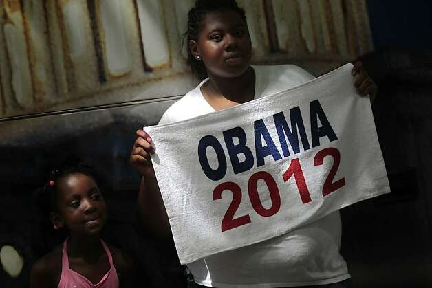 Attendee Uniq Leach, right, displays an Obama 2012 towel for a photograph while Zoe Leach looks during CarolinaFest 2012 ahead of at the Democratic National Convention (DNC) in Charlotte, North Carolina, U.S., on Monday, Sept. 3, 2012. The 2012 Democratic National Convention, which kicks off on Sept. 4, is expected to draw tens of thousands of people including nearly 6,000 delegates from across the country.