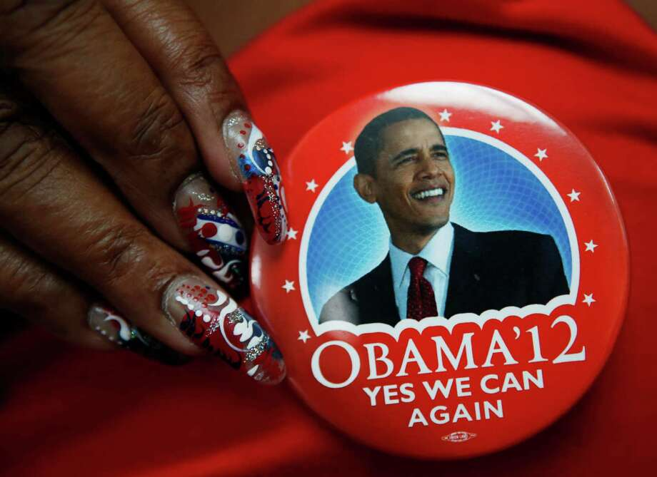 A delegate shows off her President Barack Obama button in the convention hall before the Democratic National Convention in Charlotte, N.C., on Monday, Sept. 3, 2012. (AP Photo/Jae C. Hong) Photo: Jae C. Hong, Associated Press / AP