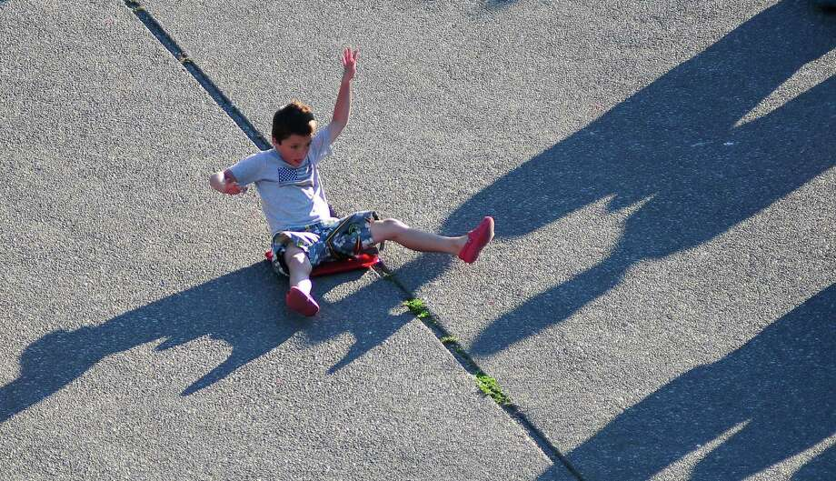 Max Sevier, 7, slides down the International Fountain pit on a plastic tray. Photo: LINDSEY WASSON / SEATTLEPI.COM