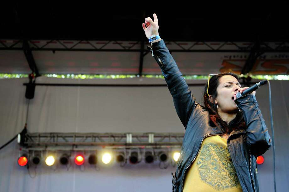 Ana Tijoux raises her arm in the air as she plays at the TuneIn Stage on the Fisher Green. Photo: LINDSEY WASSON / SEATTLEPI.COM