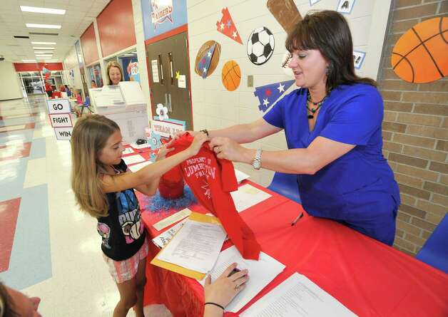 Baillie Reyes, 8, left, gets a new T-shirt from Amy Morgan, right, the school nurse at the primary school, while her mother, Ami Dobbins works on the paperwork. The Lumberton School District was registering new to the district students, for class on Wednesday, August 8, 2012. Parents came to the high school and filled out all the paperwork needed. For students going to the primary school, they were handling out T-shirts to students who were new to the district. Dave Ryan/The Enterprise Photo: Dave Ryan