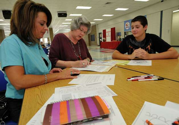 Brock Wagner, 14, right, who will be a freshman this year, watches his mother, Nicole Wagner, left, and his grandmother Linda Faraci, middle, fill out all his paperwork.  He was transferring from the Hardin-Jefferson school district. The Lumberton School District was registering new to the district students, for class on Wednesday, August 8, 2012. Parents came to the high school and filled out all the paperwork needed. For students going to the primary school, they were handling out T-shirts to students who were new to the district. Dave Ryan/The Enterprise Photo: Dave Ryan