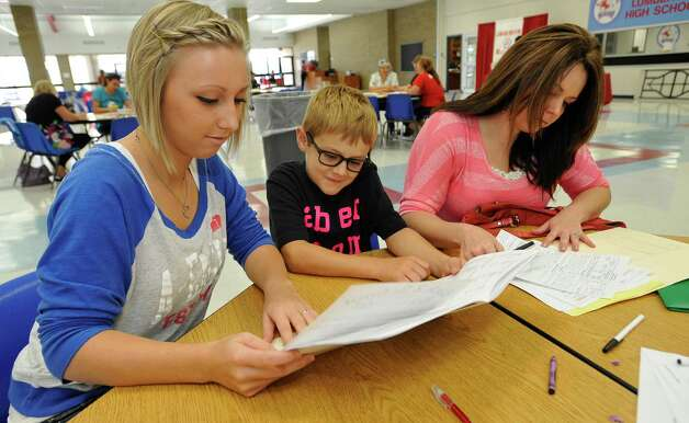 Brianne Horn, 17, left, shows her brother Colby Horn, 11, middle some information about their new schools as their mother Melissa Horn, right, fills out the needed paperwork on her children. They were coming from Silsbee. The Lumberton School District was registering new to the district students, for class on Wednesday, August 8, 2012. Parents came to the high school and filled out all the paperwork needed. For students going to the primary school, they were handling out T-shirts to students who were new to the district. Dave Ryan/The Enterprise Photo: Dave Ryan