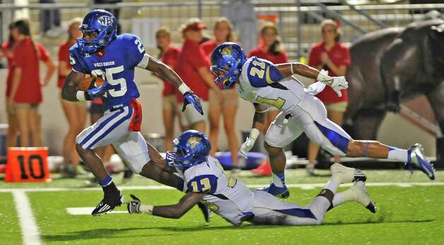 "West Brook #25, Justin Hervey, left, avoids  tackles from Ozen #13, Kourtney Williams, and #21Chris James,  as he runs downfield to score the first West Brook touchdown. Ozen High School met West Brook High School in the football season opener Friday August 31, 2012 at the Carrol A ""Butch"" Thomas Educational Support Center. At the half, Ozen was leading West Broom 13-7.  Dave Ryan/The Enterprise Photo: Dave Ryan"