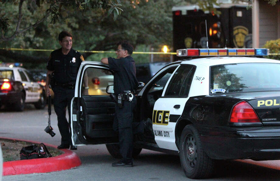 San Antonio police officers monitor a crime scene Tuesday morning September 4, 2012 at the Lincoln Village apartments on the 1700 block of Jackson Keller where a fatal shooting took place about 3:15 a.m. . Officials said a reserve Poteet police officer shot an intruder in the head in his apartment after identifying himself as an officer. The suspect died in the apartment's patio. Photo: John Davenport, San Antonio Express-News / San Antonio Express-News