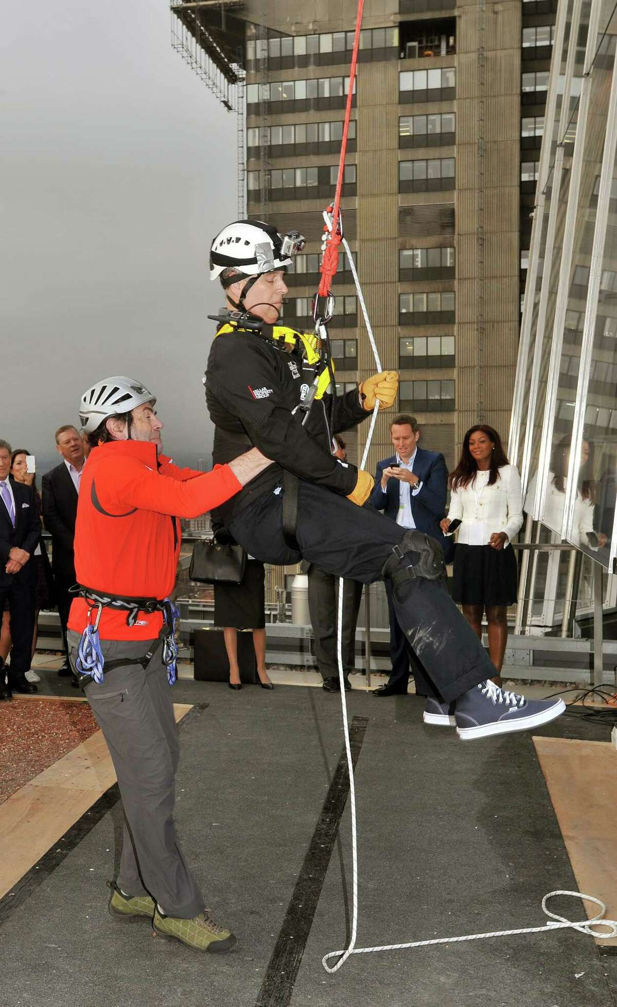 LONDON, UNITED KINGDOM - SEPTEMBER 03: Prince Andrew, Duke of York is helped by Professor David Hopkins of the Outward Bound Trust after he abseiling down the Shard for charity on September 03, 2012 in London, England. The Prince joined with 40 other people in abseiling down the tallest building for the educational charity The Outward Bound Trust and the Royal Marines Charitable Trust Fund.