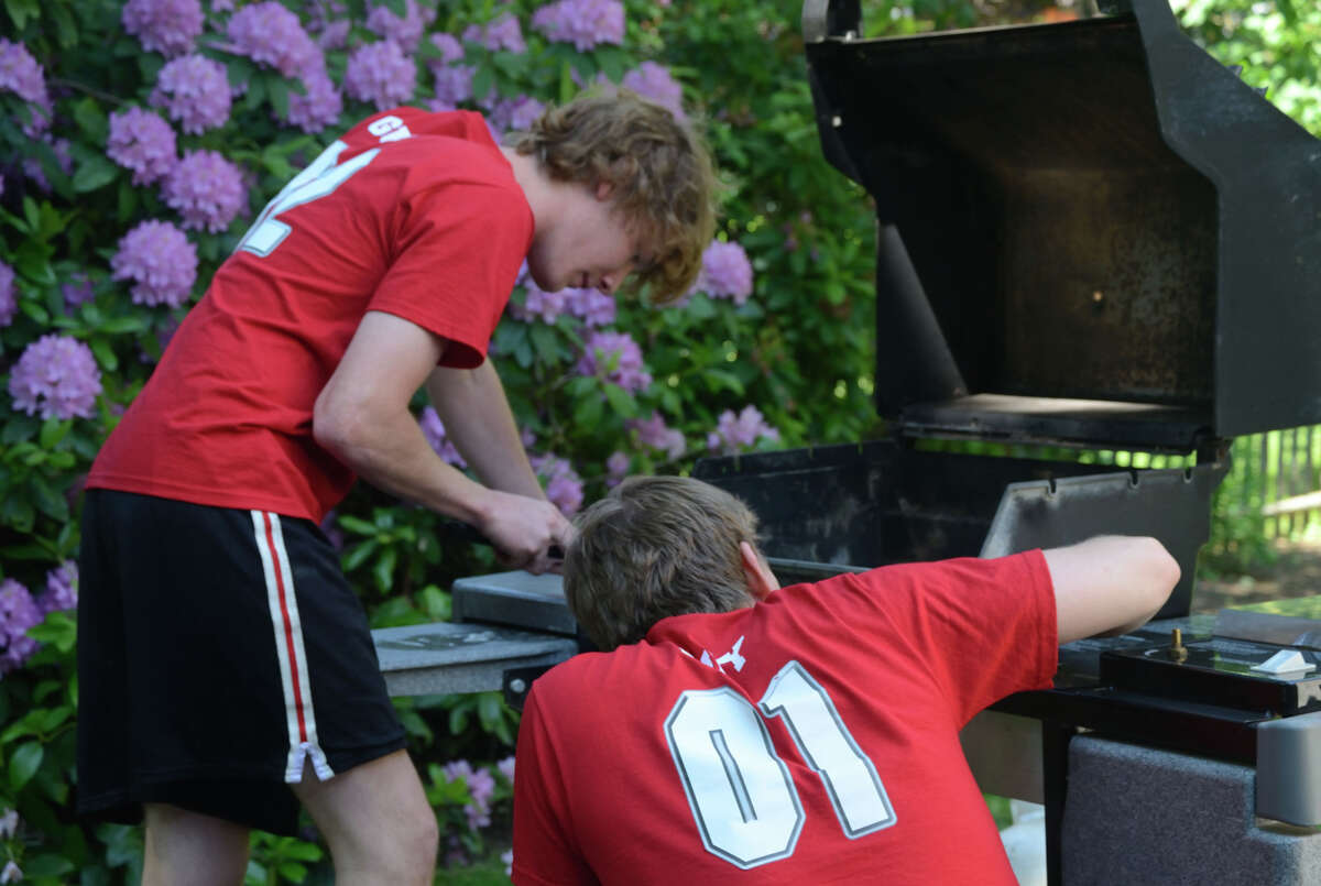 Chris Valk, left, and Kenneth Slattery, partners in Two Guys and a Grill, clean a barbeque grill for one of their clients, which number more than 140. The young entrepreneurs said it takes them 1 ½ to two hours to disassemble a grill, de-grease and clean it, and reassemble it.