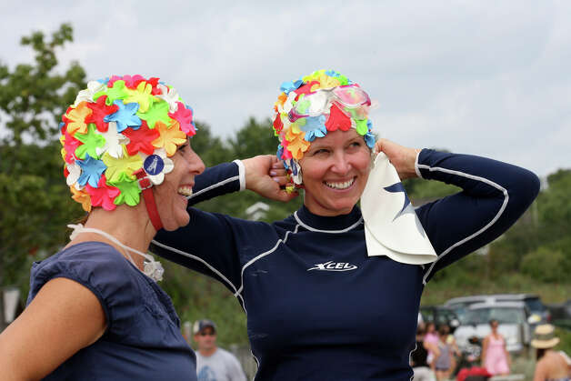 Paula Fortuna, left, and Christine McGee, put their swim caps on at the annual Arthur J. Ladrigan Swim Races and Family Fun Day at Bayley Beach in Rowayton, Conn. on Sunday, September 2, 2012. Photo: Unknown, B.K. Angeletti / Connecticut Post freelance B.K. Angeletti