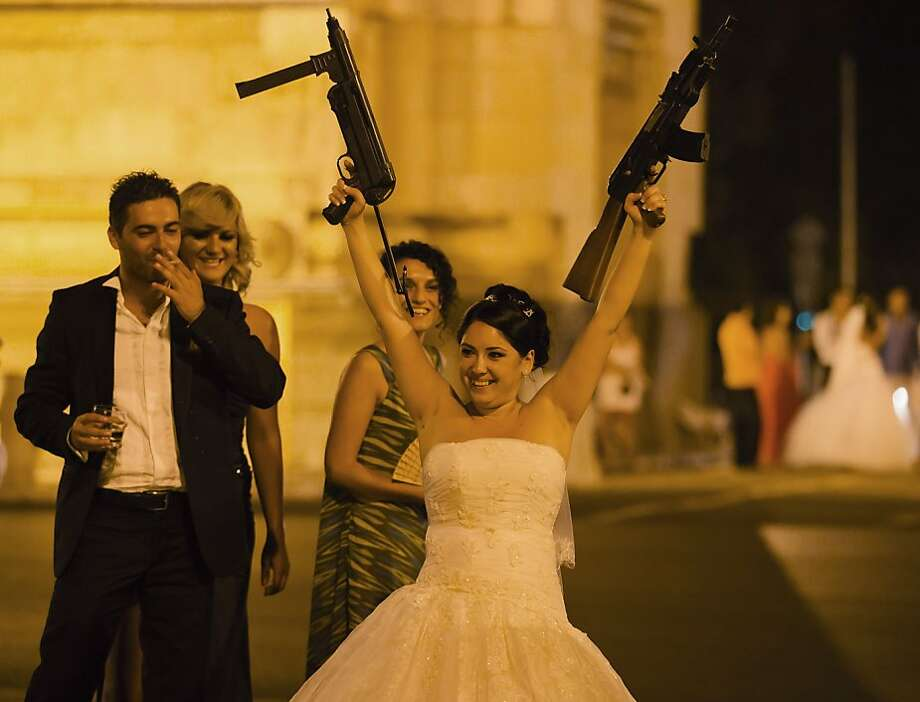 """Shotgun wedding?More like assault rifle. This Romanian bride is  celebrating at the Arch of Triumph in Bucharest after being """"kidnapped""""  on her wedding night. The tradition of snatching the bride from under  the nose of groom and guests is one of Romania's more colorful customs.  Often the groom must pay ransom - by singing a song, paying a small  amount of cash or performing another task - to free his bride. Photo: Vadim Ghirda, Associated Press"""