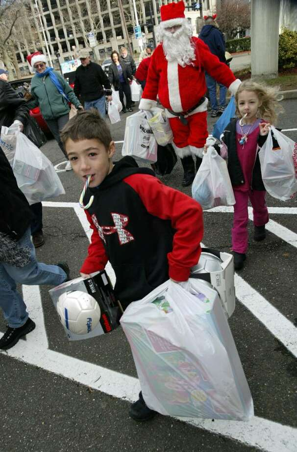 Jackson Lynch, 7, and his sister, Ella, 5, help Santa Claus ( Roy Master of Orange) carry toys into Troop G in Bridgeport, after members of the Club Corvette of Ct drove to Bridgeport with a State Police excort to drop off 50 corvettes full of toys, Sunday, Dec. 6, 2009. Photo: Phil Noel / Connecticut Post