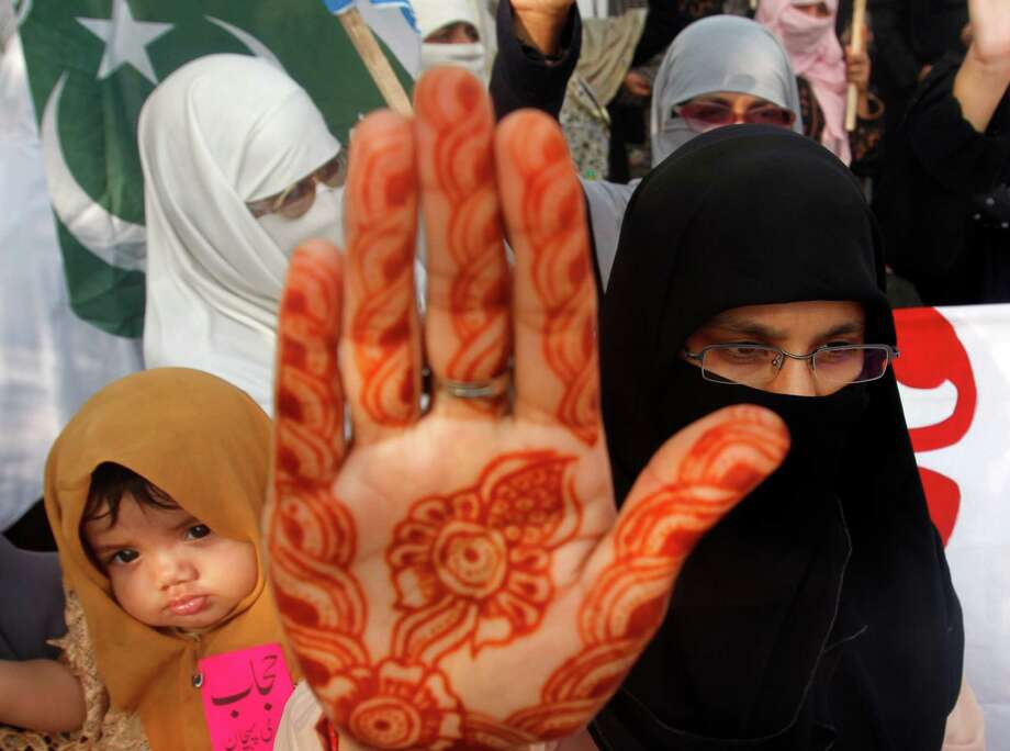 Women supporters of Pakistani religious party Jamaat-e-Islami raise their hands to take oath to continue wear hijab (veil) during a rally in Karachi, Pakistan on Tuesday, Sept. 4, 2012.  Rallies were organized nationwide to observe the Hijab (veil) Day to highlight what the group sees as the importance and value of hijab for Muslim women. (AP Photo/Shakil Adil) Photo: Shakil Adil, Associated Press / AP
