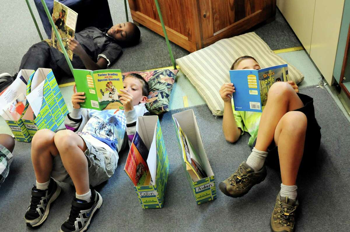 Fourth-graders Najan Hill, top, Collin Zito, center, and Aidan Krumm read on the first day of class on Tuesday, Sept. 4, 2012, at Albany School for the Humanities in Albany, N.Y. (Cindy Schultz / Times Union)