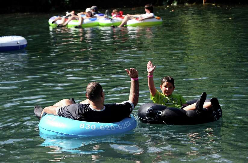 Jack Burns and his son Cameron Burns, 8, high five as they tube down the Comal River in New Braunfel