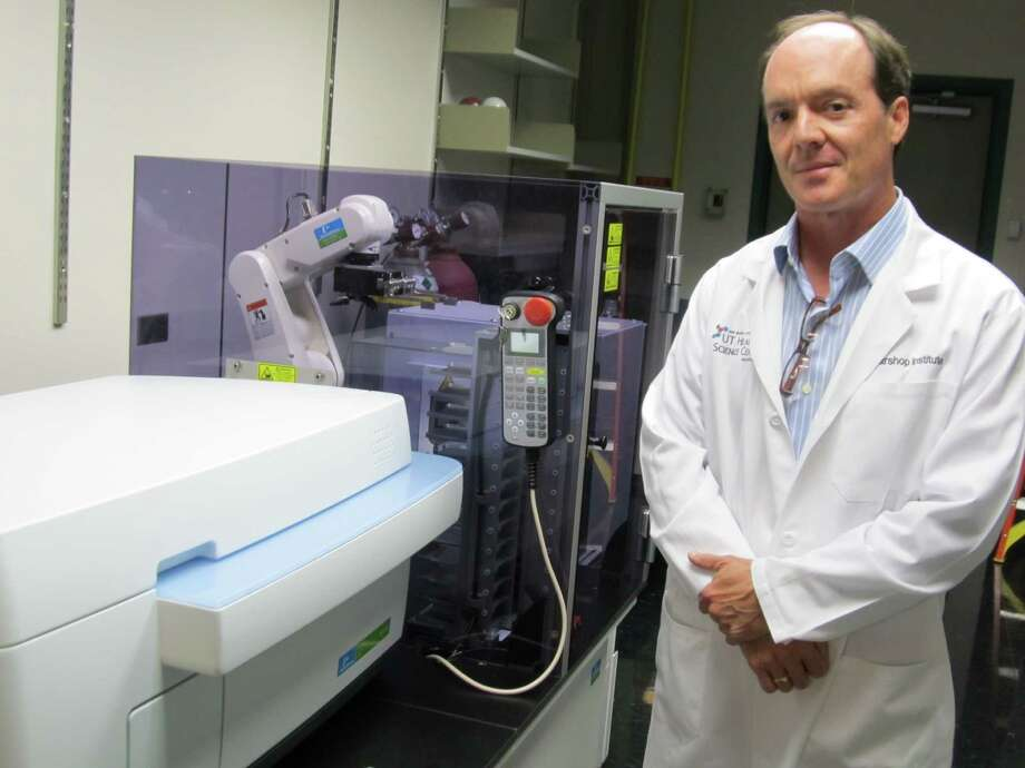 The UT Health Science CenterÕs Matthew Hart, Ph.D., high-throughput screening director for the new Center for Innovation in Drug Discovery, is pictured with a half-million-dollar PerkinElmer Operetta instrument that provides super-fine resolution for imaging of cells on slides and micro-well plates. The instrument is integrated with a robotic plate handler, a micro-plate incubator, a bar code reader and scheduling software to form a system that can screen thousands of compounds for potentially therapeutic properties. Photo: Courtesy Photo / UTHSCSA