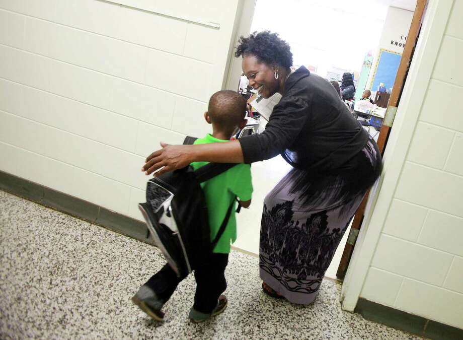 First-grade teacher Genelle Harrell welcomes Caiden Smallwood to class on the first day of school at R.N. Harris Integrated Arts/Core Knowledge Magnet School on Aug. 27, in Durham, N.C. Photo: AP