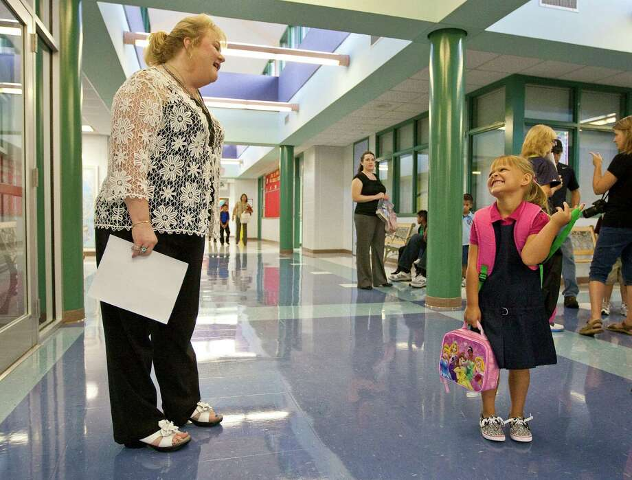 And some students are perfectly happy. Here, first-grader  Ashlynn Harrison greets Principal Beth West on the first day of school, Aug. 27, at Rustic Oak Elementary School in Pearland, Texas. Photo: AP