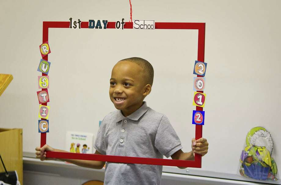 Seattle schools have their first day of classes on Wednesday. But school has already started in much of the world. Click on for views of the first day of school around the world this year and in the past. Here, Jordan Henry, a prekindergarten student at Rustic Oak Elementary School,  in Pearland, Texas, poses for a picture  on Monday, Aug. 27, with a frame his teacher made. Photo: AP