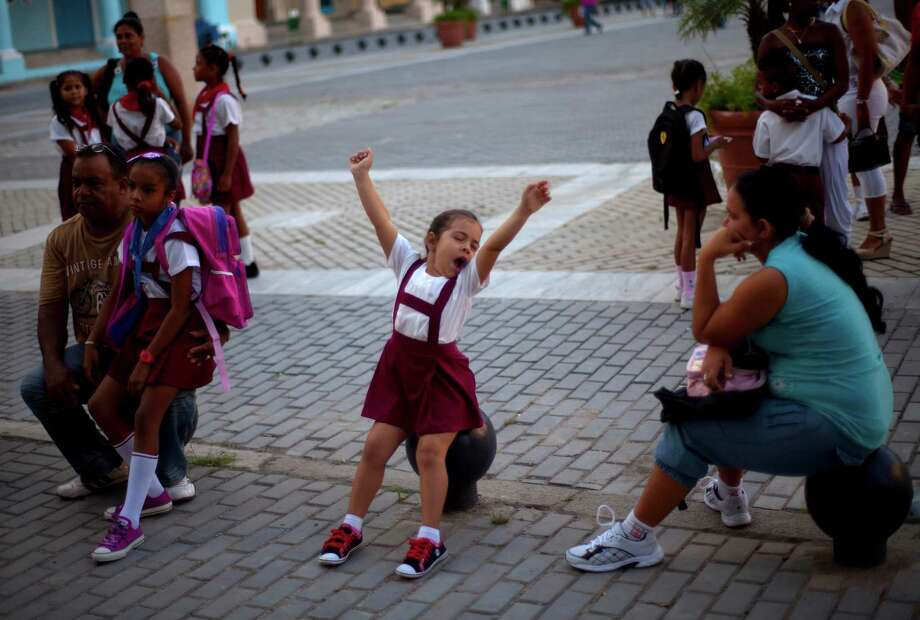 A young girl in uniform stretches out on her first day back at the Angela Landa elementary school in Old Havana, Cuba, on Sept. 3. Photo: AP