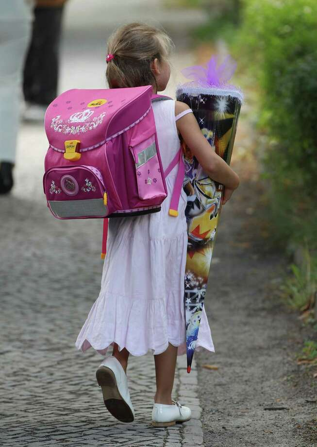 "Finally, the first day of school is done. Sarah, 5, carries a ""Schultuete,"" a conical container filled with sweets and other goodies, after attending her first day of first grade on Aug. 11 in Berlin. Photo: Sean Gallup, Getty Images / 2012 Getty Images"