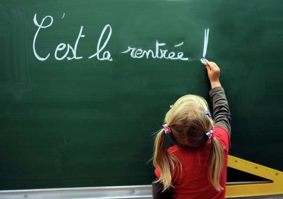 "A girl writes on the blackboard ""C'est la rentrée"" (Its the Start of the school year) at the school Jules Ferry in Bethune, France, on Aug. 28. Photo: DENIS CHARLET, AFP/Getty Images / 2012 AFP"