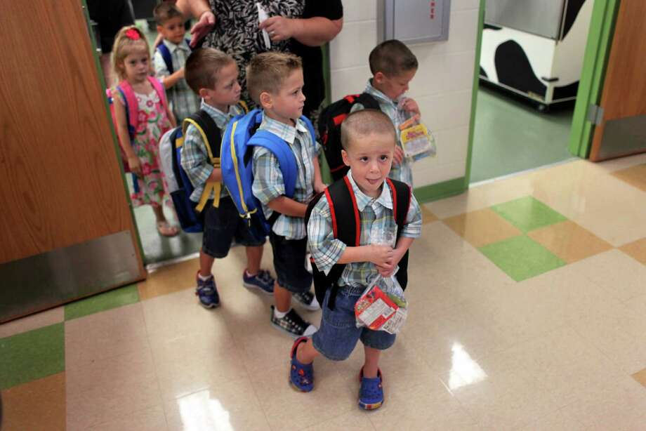 Byler sextuplets Charlie, front, Ryan, top right, Brady, Eli, Mackenzie and Jackson head toward class with mother Karoline Byler on their first day of kindergarten, Monday, Aug. 20, 2012, at Double Branch Elementary in Wesley Chapel, Fla. Photo: AP
