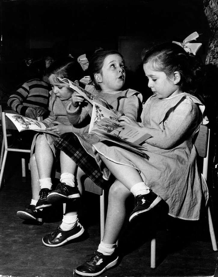 The identical Newman triplets have a look at some books on their first day of school, Feb. 4, 1954. Photo: Chris Ware, Getty Images / Hulton Archive