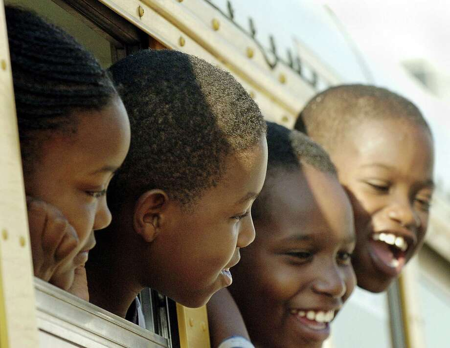 Hurricane Katrina evacuees look out from a departing school bus on the first day of school, Sept. 8, 2005, outside the Reliant Center in Houston, Texas. Photo: STAN HONDA, AFP/Getty Images / 2010 AFP
