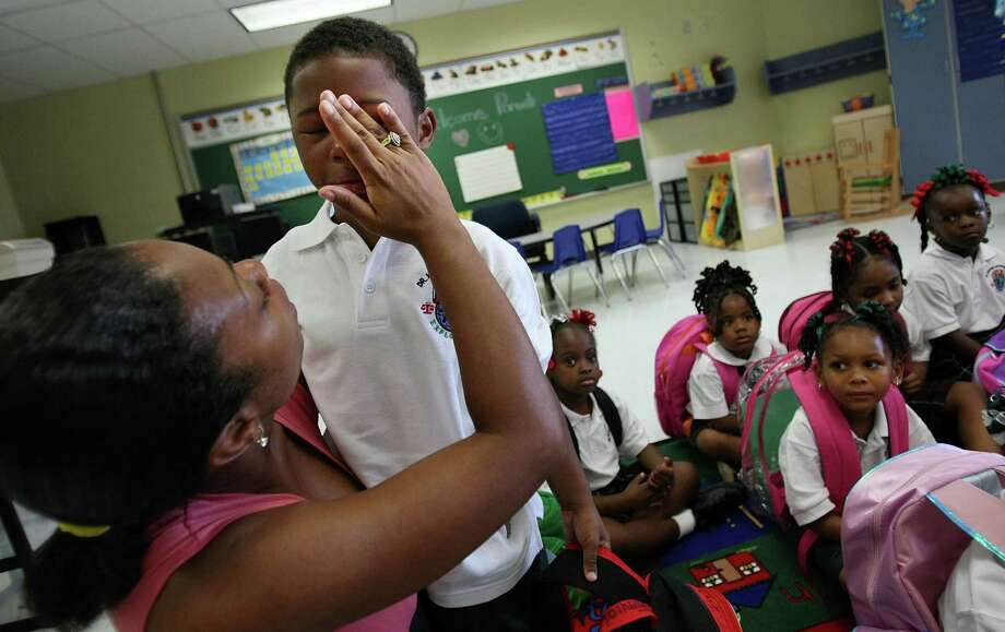 Kindergartner Jeremiah Johnson is comforted by godmother Nikkisha Breaux on his first day of school on August 20, 2007 at Dr. Martin Luther King Jr. Charter School for Science and Technology in the Lower 9th Ward in New Orleans, La. Photo: Mario Tama, Getty Images / 2007 Getty Images