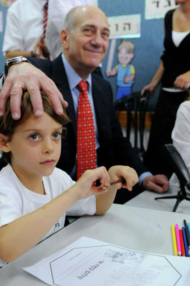 This child doesn't seem so sure what Israeli Prime Minister Ehud Olmert is doing on the first day of school, Sept. 1, 2008 in Nazareth, Israel. Photo: Pool, Getty Images / 2008 Getty Images