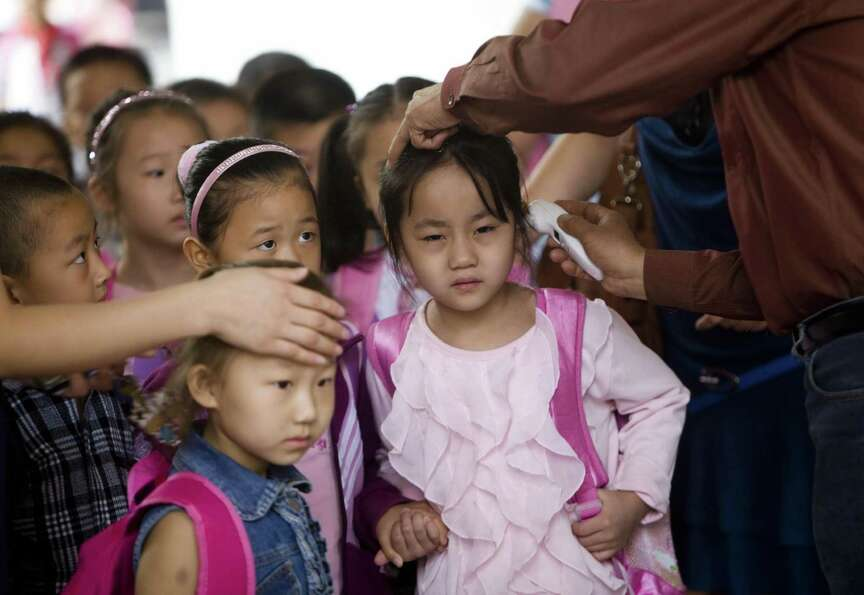 Chinese children have their temperature taken as they arrive for the first day of school after the l