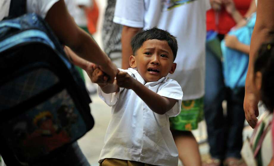 A grade-one student cries as his sister pulls him during the first day of school at an elementary school in Manila, the Philippines on June 15, 2010. Photo: NOEL CELIS, AFP/Getty Images / 2010 AFP
