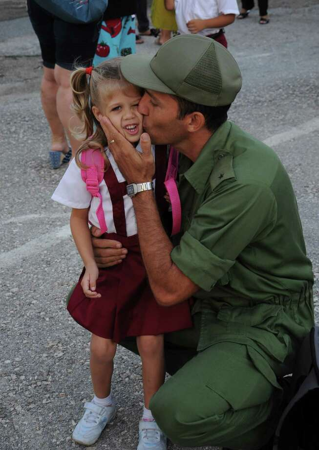 Now it's time to say goodbye to mom and dad. Here, a soldier gives his daughter a kiss on her first day of school in Havana, Cuba, on September 5, 2011. Photo: STR, AFP/Getty Images / 2011 AFP