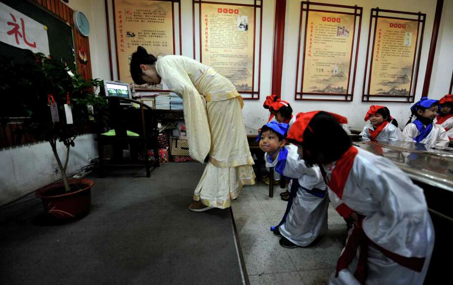 "Chinese students wear Han dynasty costumes as they undergo a ""kaibi"" or ""start to write"" ceremony to pay respects to Confucius on the first day of a new school term on Feb. 9, in Beijing. Photo: STR, AFP/Getty Images / 2012 AFP"
