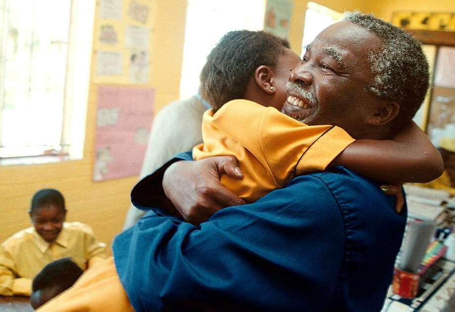 South African President Thabo Mbeki went further, hugging a child on Jan. 16, 2002, the first day of school at Katholong outside Johannesburg. Photo: SCHALK VAN ZUYDAM, AFP/Getty Images