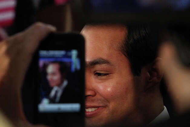 An onlooker records video of Mayor Julian Castro on an iPhone as he is interviewed at Time Warner Cable Arena before the start of the Democratic National Convention in Charlotte, NC on Tuesday, Sept. 4, 2012. Photo: Lisa Krantz, San Antonio Express-News / San Antonio Express-News