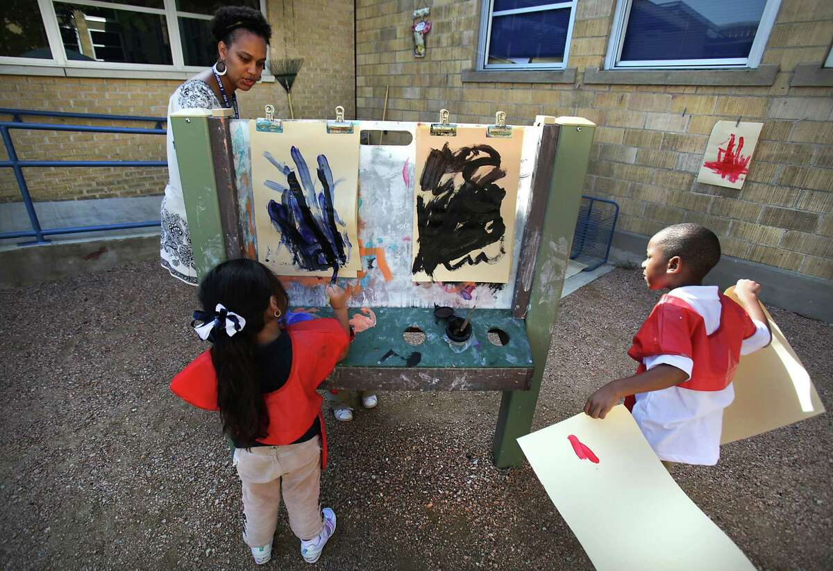Chaka Burroughs, a pre-K teacher at the Carroll Early Childhood Center in the SAISD, assists students Miliana Vargas (left) and Jonathan Toney with painting in the garden area at the school.
