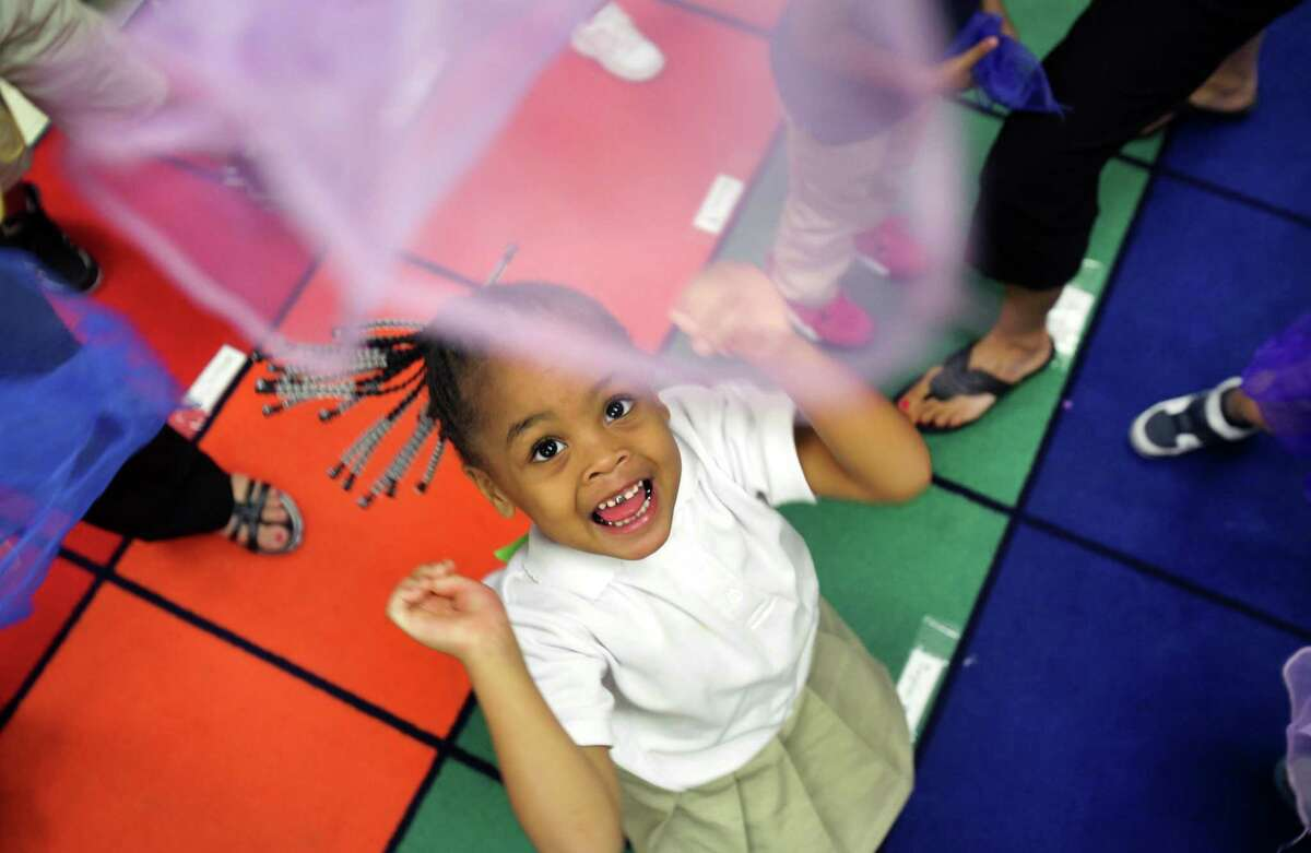 Pre-K student Teighan Davis toys with a lavender scarf during group play in her class at Carroll Early Childhood Center in the San Antonio Independent School District.