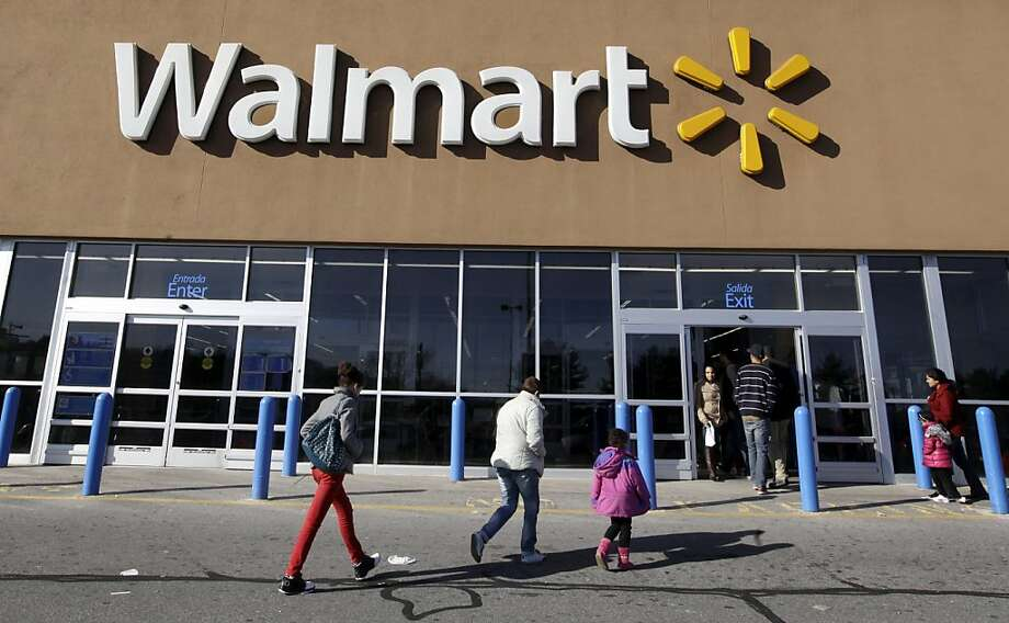 In this file photo, customers walk into and out of a Wal-Mart store in Methuen, Mass. Photo: Elise Amendola, Associated Press