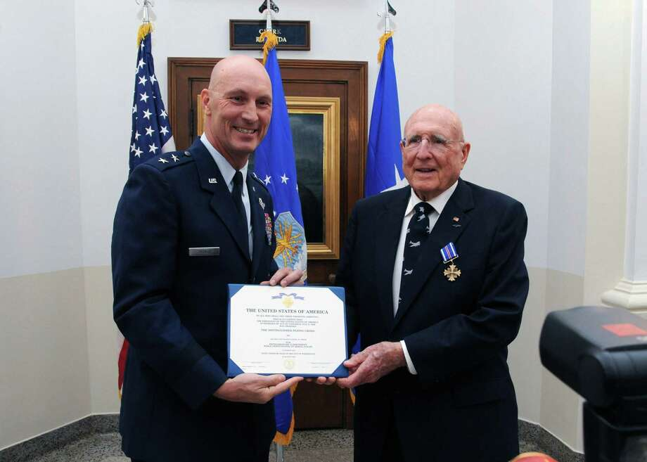 Maj. Gen. Timothy Zadalis hands Samuel Smith a proclamation of his receipt of the Distinguished Flying Cross, which he earned by flying 24 combat missions over Nazi Germany during World War II. Photo: Rich McFadden, Courtesy Photo