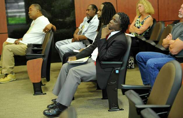 Ricky Jason, center, and Sean Westbrooks, beside him, listen as Ward II Councilman Mike Getz addresses the council over comments made at last week's meeting.  Beaumont City Council met Tuesday afternoon September 4, 2012. Ricky Jason and the People of Colors  attended the meeting and spoke to Councilman Mike Getz and the rest of the council about his behavior at former BISD Superintendent Carrol Thomas' retirement party. The group then held a press conference immediately after the meeting.   Dave Ryan/The Enterprise Photo: Dave Ryan