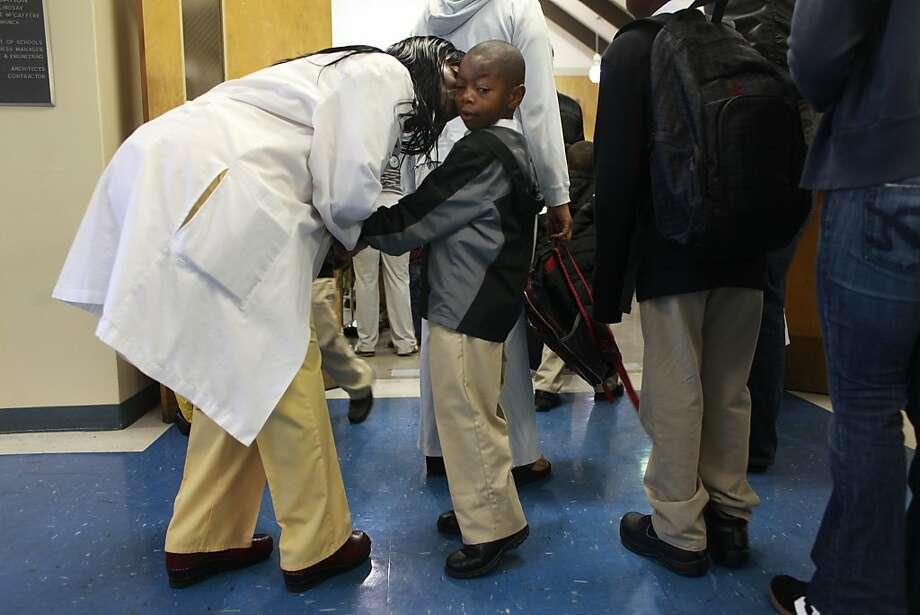 Anastasia Perrilliat kisses son Carlton Jr. as he begins kindergarten at the new 100 Black Men Community School in Oakland. Photo: Mike Kepka, The Chronicle