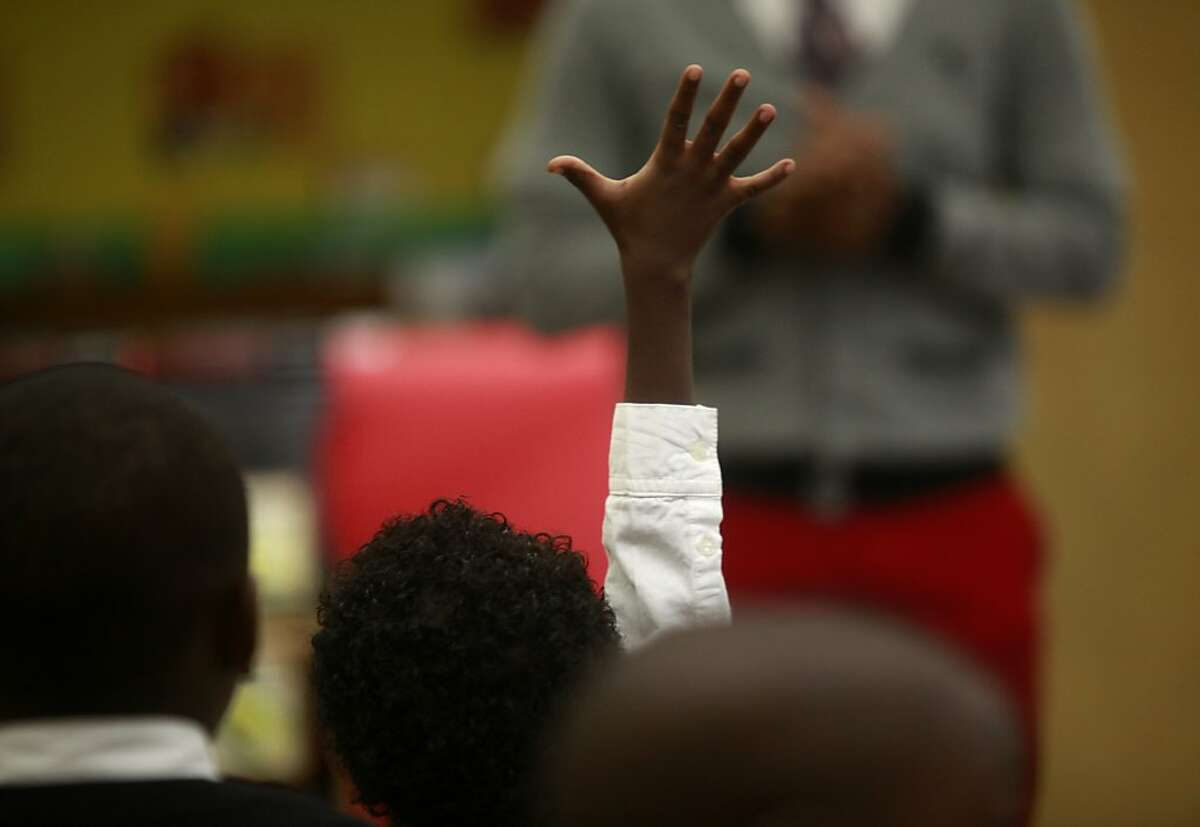 Kindergarten teacher, Xavier Buster takes a question from at eager student on the first day of school at The 100 Black Men Community School on Tuesday Sept. 04, 2012 in Oakland, Calif.