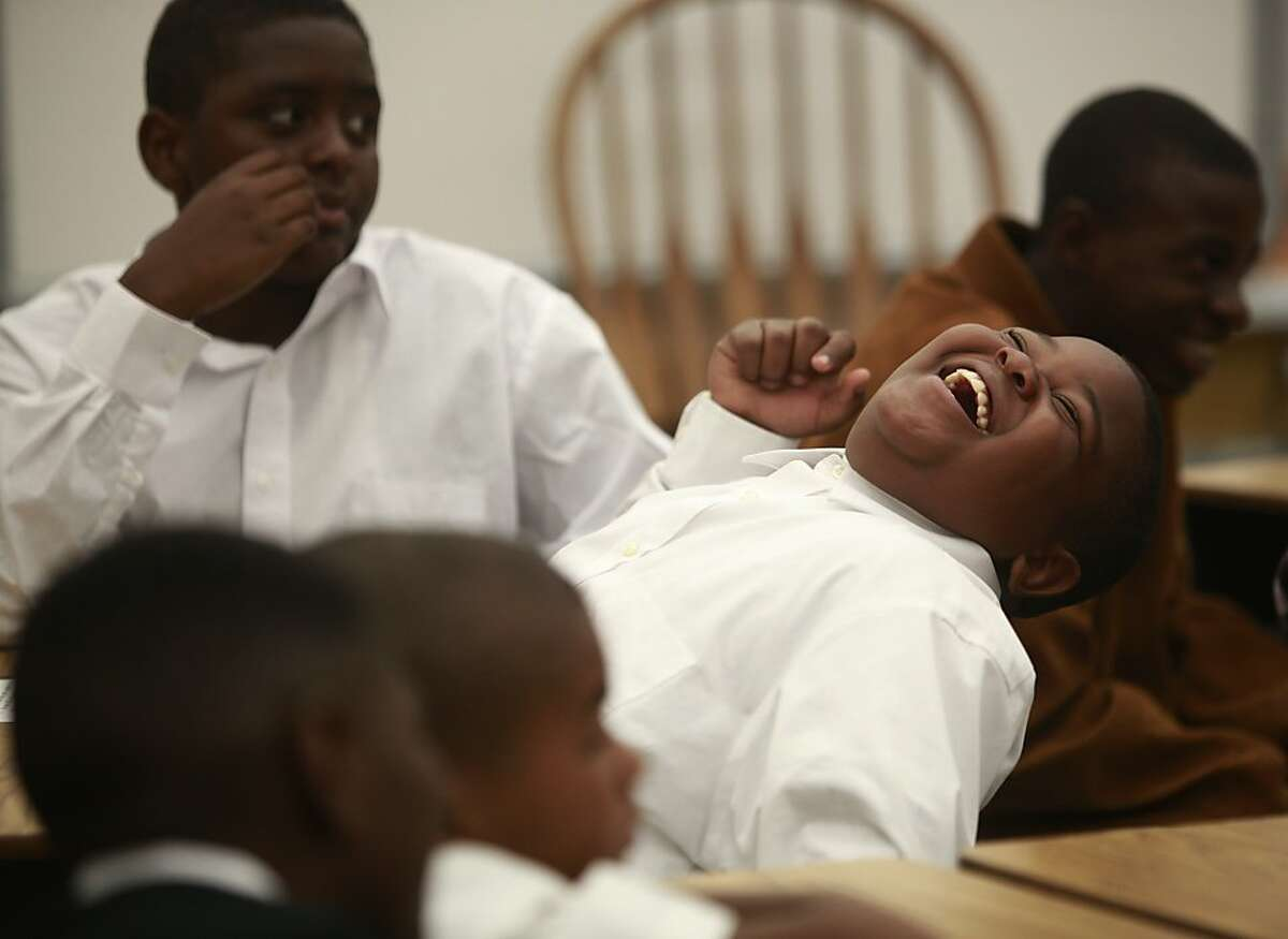 Charlie Henderson, 11, laughs during a discussion with his 6th grade teacher on the first day of school at The 100 Black Men Community School on Tuesday Sept. 04, 2012 in Oakland, Calif.